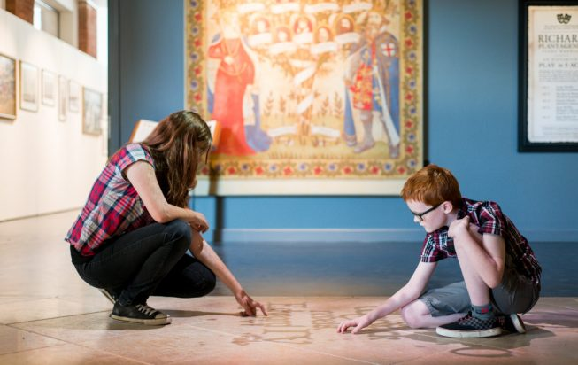 Two children looking at the floor