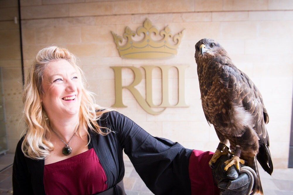 A woman holding a bird of prey