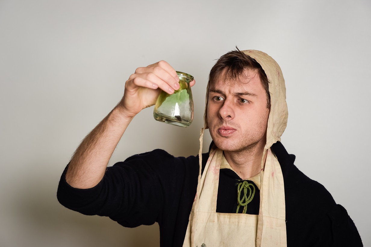 A man, dressed in medieval costume, holding a potion bottle