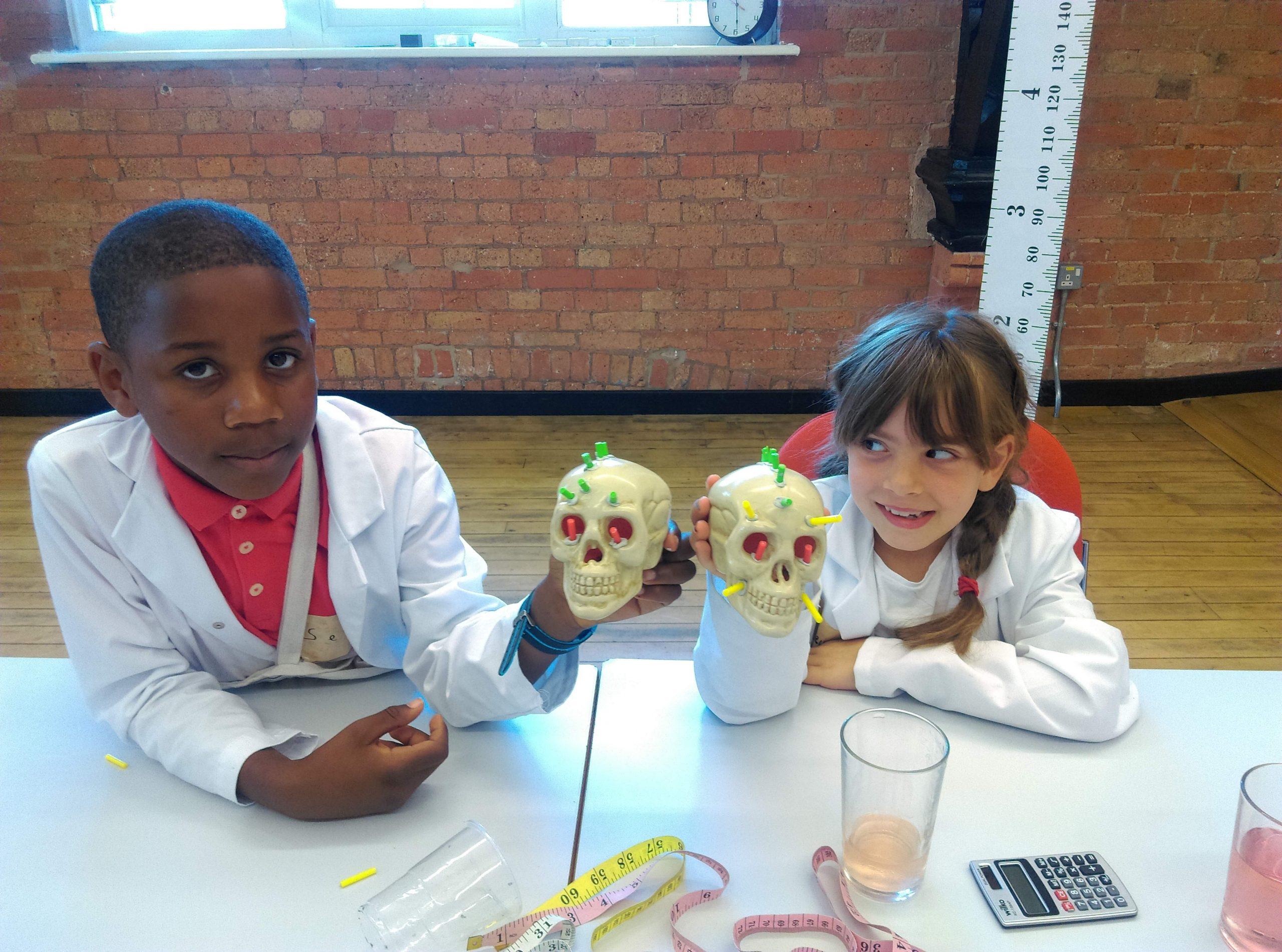 Two children holding models of skulls